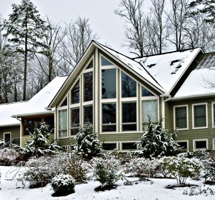 A large, modern, house in the winter snow.